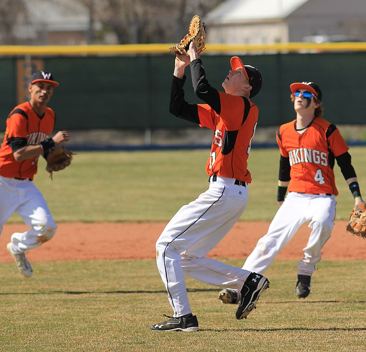 Payce Mortensen catches a ball at second base while Quinn Howell and Daniel Lopez look on.