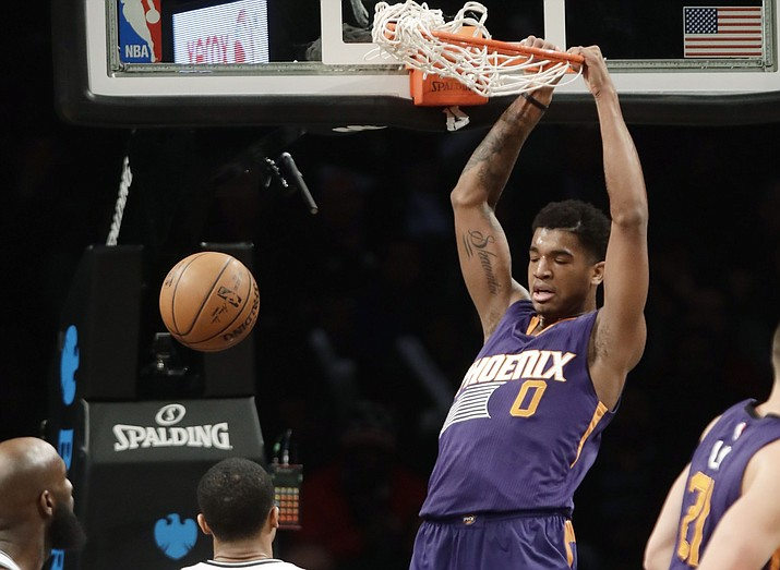 Phoenix Suns' Marquese Chriss (0) dunks the ball in front of Brooklyn Nets' Quincy Acy, left, and Spencer Dinwiddie, center, during the first half of an NBA basketball game Thursday, March 23, 2017, in New York. (Frank Franklin II/AP)