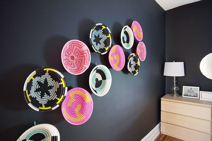 This undated photo provided by AphroChic shows a room in a Crown Heights, New York home which placed colorful baskets against a dark wall for a graphic punch. (Patrick Cline/AphroChic via AP)