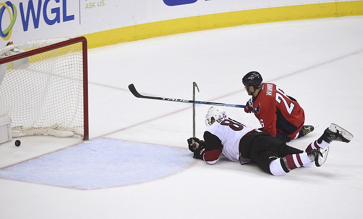 Washington Capitals left wing Daniel Winnik (26) scores into empty net as Arizona Coyotes left wing Jamie McGinn (88) defends during the third period of an NHL hockey game Saturday, March 25, in Washington.