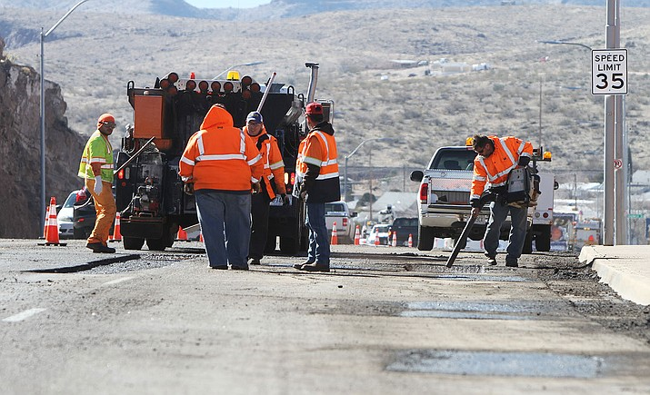City street crews work on filling potholes on Andy Devine Avenue Jan. 17.