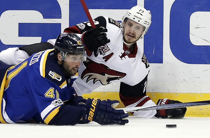 St. Louis Blues' Robert Bortuzzo (41) and Arizona Coyotes' Oliver Ekman-Larsson, of Sweden, slide along the ice while chasing after a loose puck during the first period Monday, March 27, in St. Louis. (Jeff Roberson/AP)