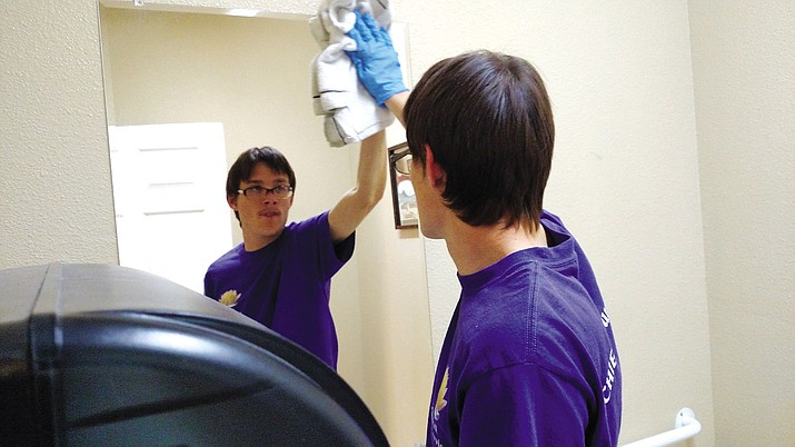 Sean Monahan wipes down a mirror during his shift at the closed Achieve Human Services office. He was one of 15 people with intellectual and development disabilities who lost their jobs.