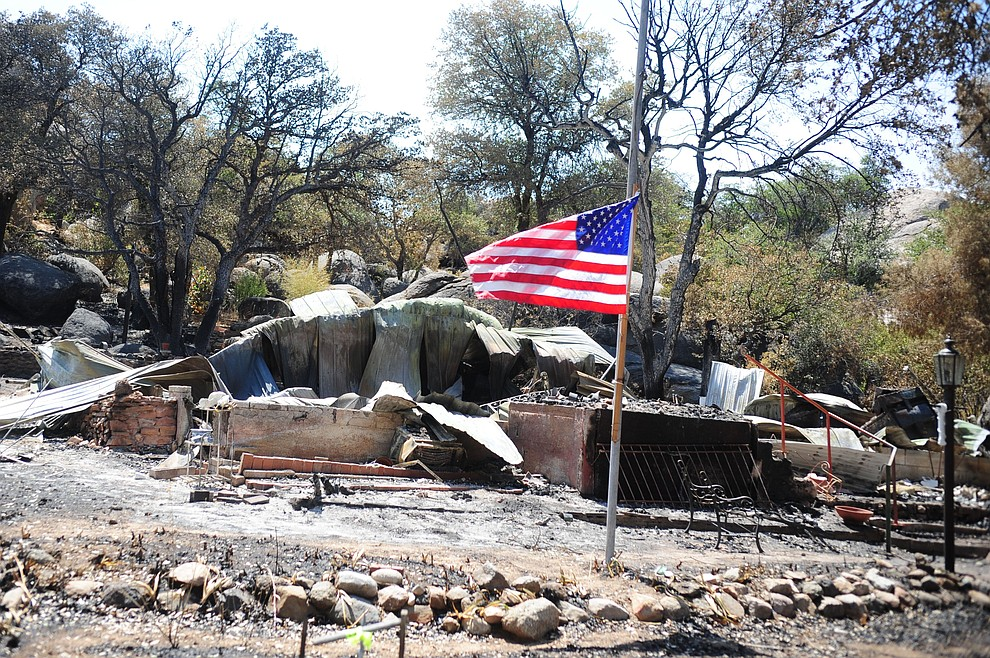 Yarnell - July 10, 2013.Les Stukenberg/The Daily Courier.The American Flag flies at half staff at the home of Stephan and Donna Holloway that burned in the Yarnell Hill fire but their thoughts are with the families of the 19 Granite Mountain Hotshots who died trying to stop the fire.