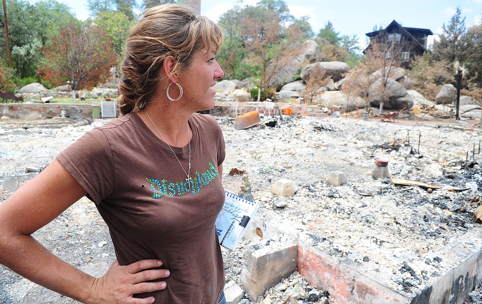 Yarnell, Ariz. - July 23, 2013.Les Stukenberg/The Daily Courier.Bonnie Tyree, from Skull Valley, looks around the remains of one of the burned homesites that she, her husband and two boys are helping to clean up in Yarnell.