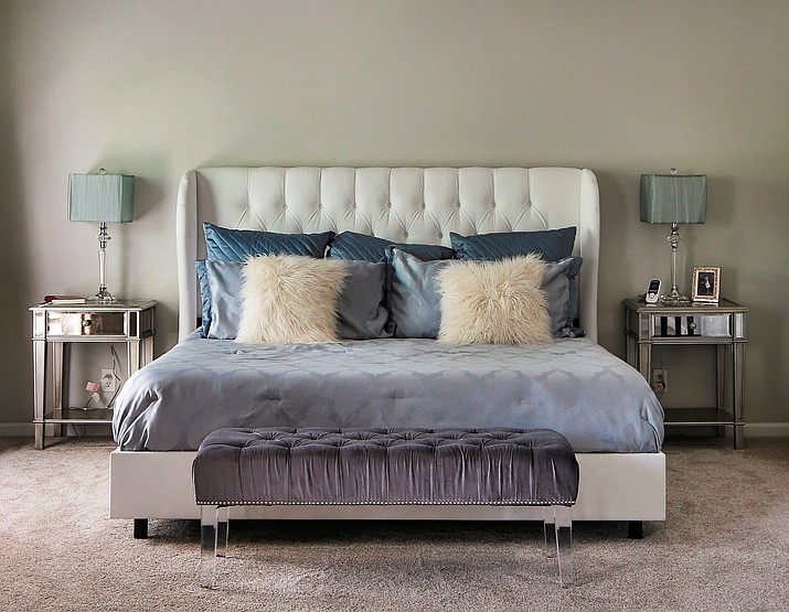 This undated photo provided by Interiors by Design shows a Lucite bench at the end of a bed which adds a whimsical touch while also providing a pop of color and texture without the visual weight of a normal piece of furniture. (Nick Schale/Interiors by Design via AP)