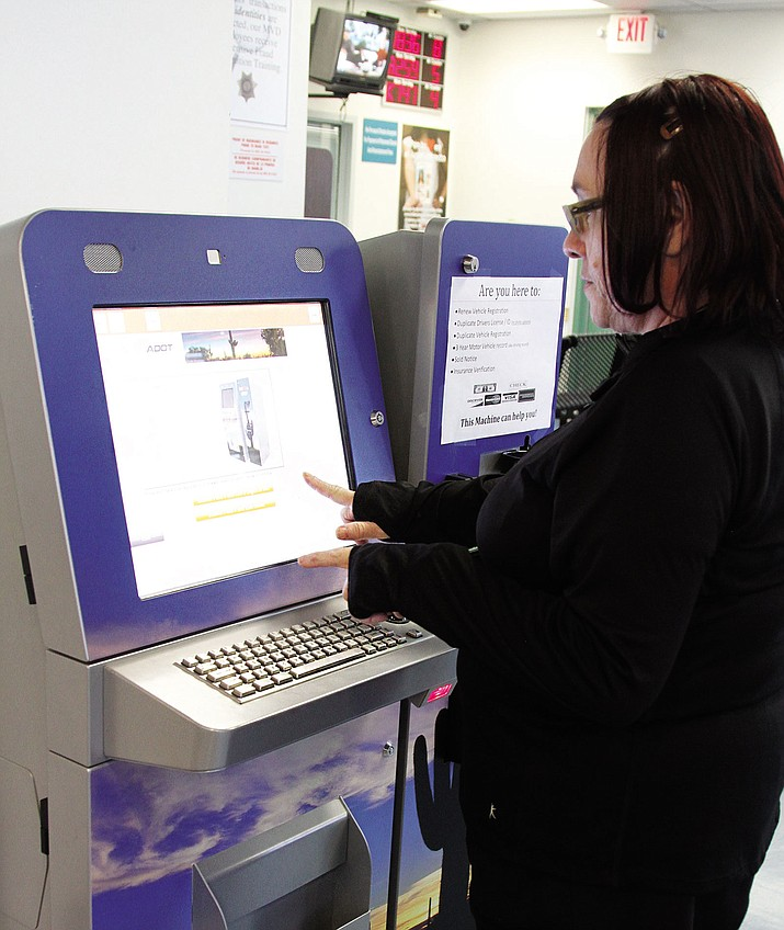 Motor Vehicle Division employee Inez Peeler demonstrates using the self-service kiosk at the MVD office in Kingman Tuesday.