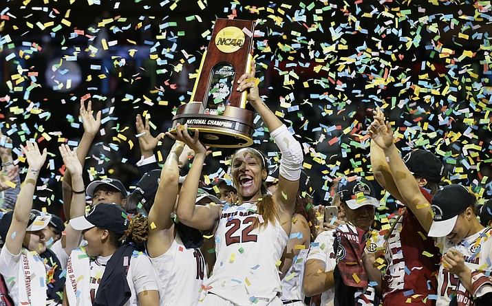 South Carolina forward A'ja Wilson (22) holds the trophy as she and her teammates celebrate a win over Mississippi State in the final of NCAA women's college basketball tournament, Sunday, April 2, in Dallas.