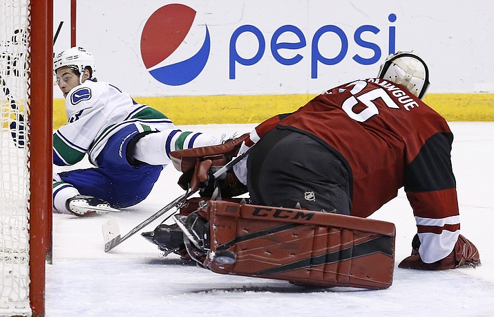 Arizona Coyotes' Louis Domingue, right, makes a save on a shot by Vancouver Canucks' Griffen Molino, left, during the first period of an NHL hockey game Thursday, April 6, 2017, in Glendale.