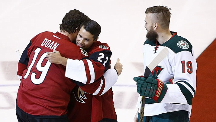 Craig Cunningham (22), the 26-year-old captain of the Tucson Roadrunners, the Arizona Coyotes' AHL affiliate, gets a hug from Coyotes team captain Shane Doan, left, after Cunningham dropped the puck in an opening ceremony as former Coyotes player and current Minnesota Wild player Martin Hanzal, right, looks on prior to an NHL hockey game Saturday, April 8, in Glendale. Just five months ago Cunningham was fighting for his life after collapsing on the ice during pregame warmups.