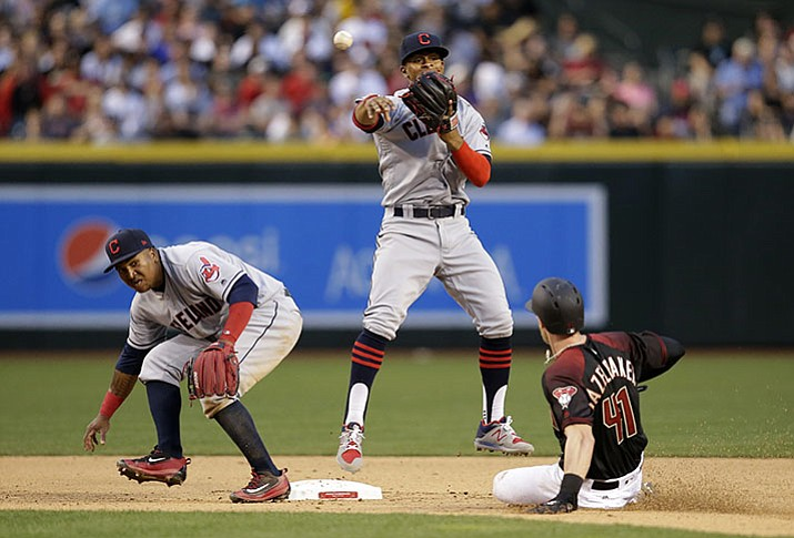 Cleveland Indians shortstop Francisco Lindor turns the double play while avoiding second baseman Jose Ramirez, left, and Arizona Diamondbacks right fielder Jeremy Hazelbaker in the fifth inning Saturday, April 8, in Phoenix.