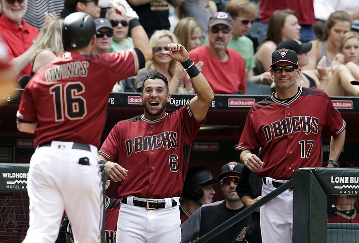 Arizona Diamondbacks' Chris Owings (16) celebrates with David Peralta (6) and manager Torey Lovullo (17) after hitting a solo home run against Cleveland in the sixth inning of a baseball game, Sunday, April 9.