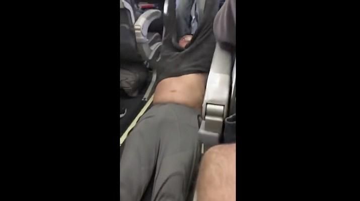 This Sunday, April 9, image made from a video provided by Audra D. Bridges shows a passenger being removed from a United Airlines flight in Chicago. Video of police officers dragging the passenger from an overbooked United Airlines flight sparked an uproar Monday on social media, and a spokesman for the airline insisted that employees had no choice but to contact authorities to remove the man.