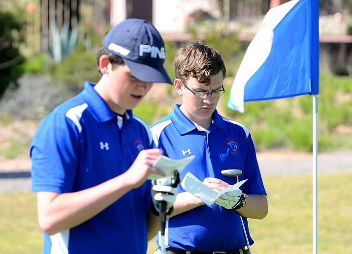 Chino Valley golfers Wyatt Dodds, left, and Jeffrey Shumate record their scores while the Cougars played rival Camp Verde at Verde Santa Fe Golf Course on Monday, April 10, in Cornville. (Vyto Starinskas/Independent)