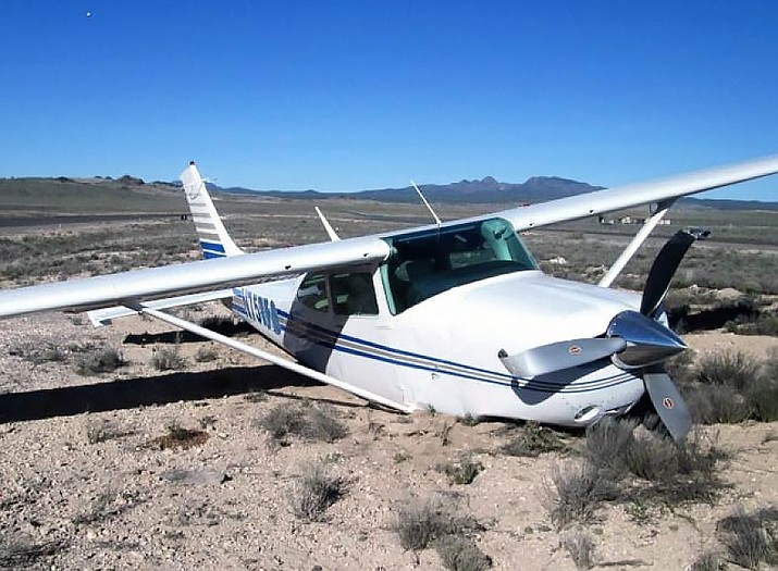 A damaged Cessna aircraft sits on the ground in Seligman after its pilot forgot to put the aircraft's landing gear down.