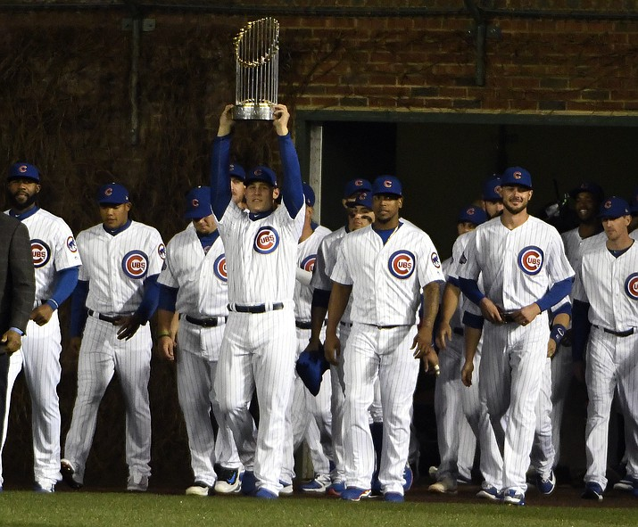 Chicago Cubs first baseman Anthony Rizzo (44) carries the 2016 World Series Championship trophy before a baseball game between the Chicago Cubs and the Los Angeles Dodgers on home opening day Monday, April 10, in Chicago. (David Banks/AP)