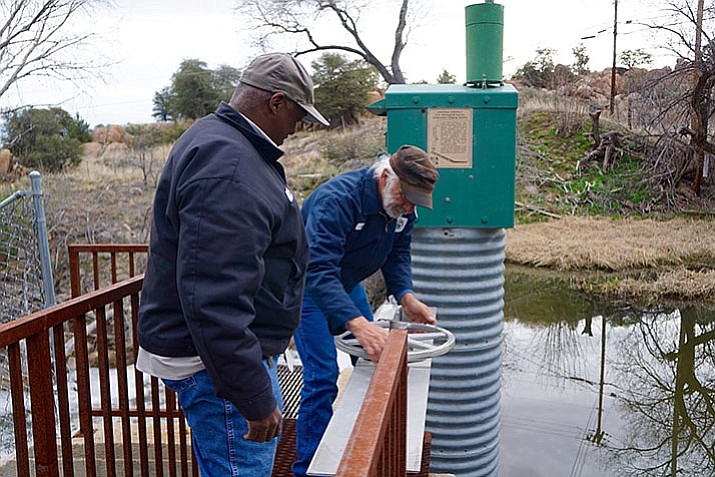 City of Prescott employees John Johnson, left, and Al Fishback open a valve that allows spill-over water from Watson Lake Dam to flow into the city's recharge field near the airport. Because of changes in regulations and the environment of water and sewer options since 1980, The city has seen significant increases in costs associated with implementing drinking water treatment, increased complexity of treating wastewater flow and increased aquifer recharging operations.