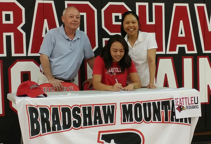 Bradshaw Mountain's Anne Transier signs her letter of intent to play golf for Seattle University on Thursday, April 14, in Prescott Valley. Parents Tom and Juliet Transier are by her side. (Doug Cook/Courier)