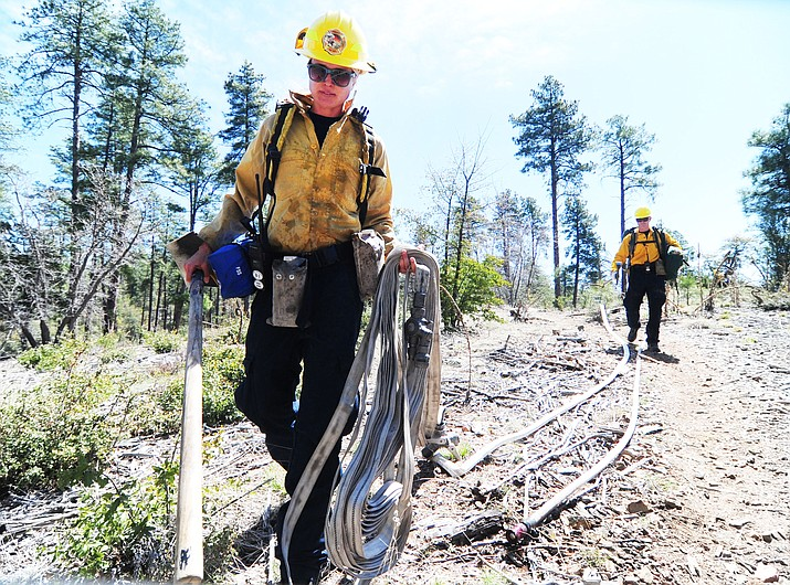 City of Prescott firefighters Jamie Wallace and Parker Moore start a hose lay during the annual Basin OPs Drill near Goldwater Lake in Prescott.  (Les Stukenberg/Courier)