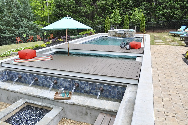 This undated photo provided by Chip Wade and Wade Works shows a pool area with movable platforms, and concealable hot tub, which make for a multi-use backyard in Johns Creek, Ga., that cleverly maximizes the square footage. (wadeworkscreative.com/Chip Wade via AP)