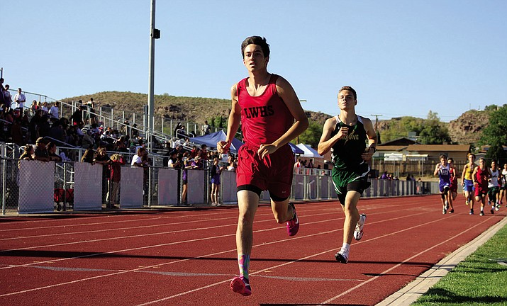 Lee Williams' Zach Moyd, left, leads the 1,600-meter Wednesday at Lee Williams High School. Moyd finished in 4:47.57 to take first place.