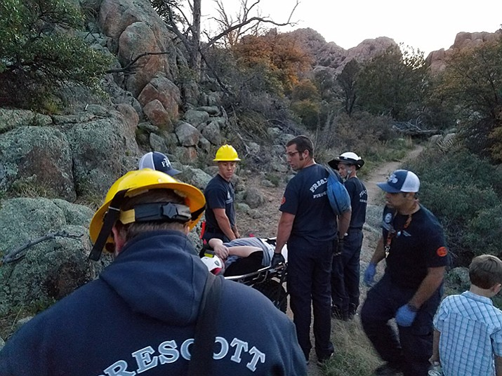 Rescue crews work to move a Prescott woman to safety after she fell hiking the Constellation Trail with her grandson.