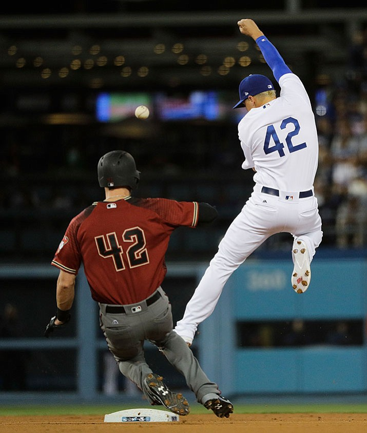Los Angeles Dodgers' Enrique Hernandez, right, misses a throw from Corey Seager as Arizona Diamondbacks' Jeremy Hazelbaker safely takes second base during the fifth inning of their game Saturday, April 15, in Los Angeles.
