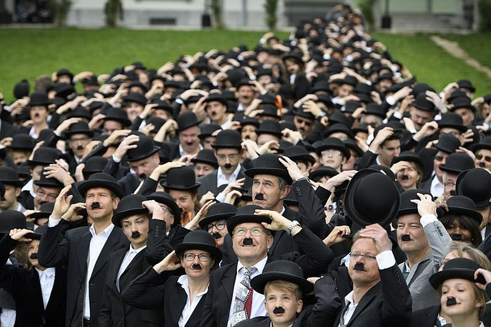 "662 people dressed as Charlie Chaplin pose for a group photo in front of the Manoir de Ban during an attempt of the world's largest gathering of people dressed as The Tramp on the occasion of Charlie Chaplin's birthday, and to celebrate the first year of the museum ""Chaplin's World by Grevin,"" in Corsier-sur-Vevey, Switzerland, Sunday, April 16, 2017."