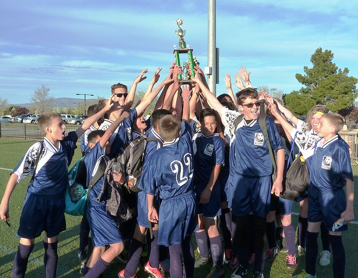 The Acorn Montessori School co-ed soccer team celebrates winning a trophy.