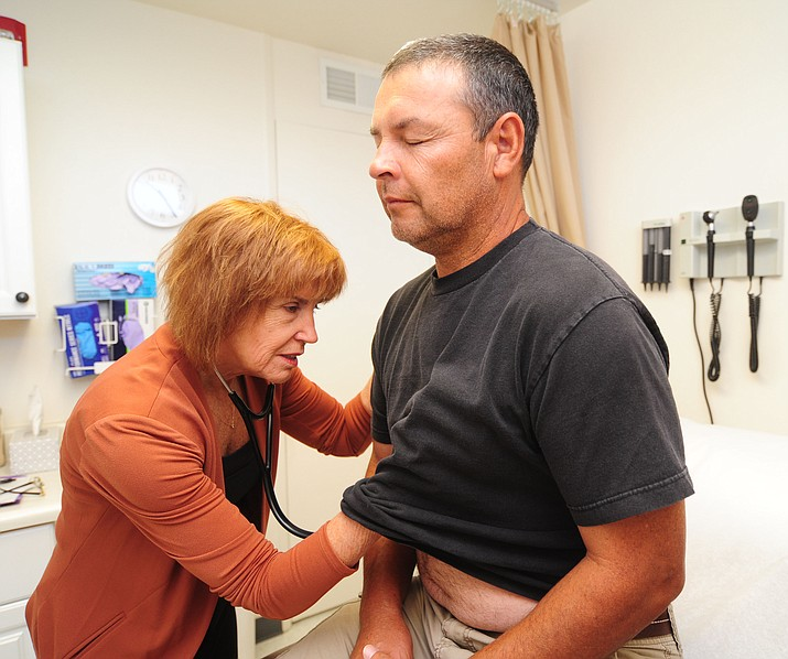 Prescott Health Clinic owner and nurse practioner Rebecca Oldani checks the heartbeat of patient Jesse Serrano who has high deductible health insurance Tuesday, April 18 in Prescott.  (Les Stukenberg/Courier)