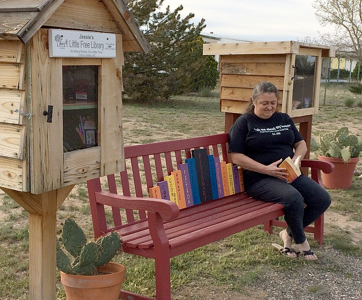 Jessie Spring, lover of books, rests on the bench that sits between her Little Free Library and her Blessing Box at 2100 N. Maricopa St. off West Road 3 North.