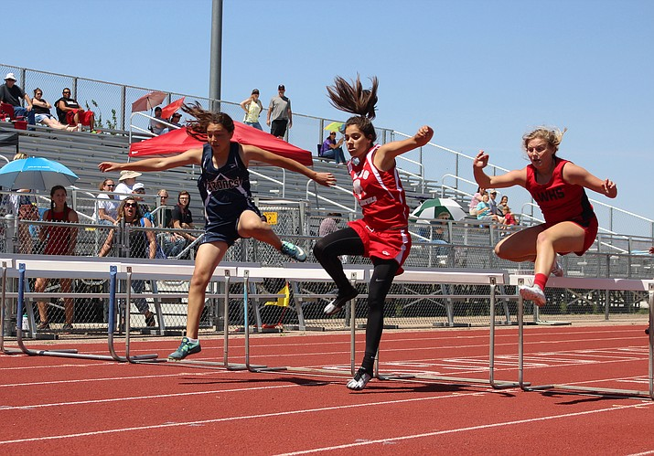 Lee Williams' Bryce Shuffler, right, runs the 300-meter hurdles during the Route 66 Invite Saturday at Kingman High School. Shuffler finished in 52.16 for third place.