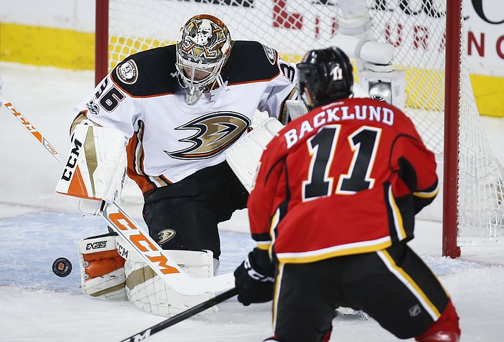 Anaheim Ducks goalie John Gibson, left, deflects a shot from Calgary Flames' Mikael Backlund, of Sweden, during the second period of Game 4 in a first-round NHL hockey Stanley Cup playoff series Wednesday, April 19, in Calgary, Alberta.