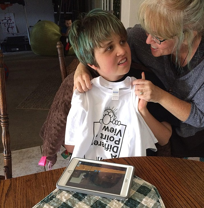 Keagan Sweeney and her mother, Joanna, smile over her T-shirt creation to honor National Autism Awareness Month.