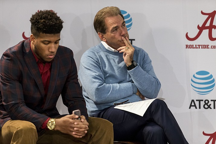 In this Jan. 13, 2017, file photo, Alabama NCAA college football coach Nick Saban sits beside Alabama defensive back Marlon Humphrey as Alabama offensive lineman Cam Robinson speaks to the media in Tuscaloosa, Ala. Alabama's defense figures to resume its dominant ways during the NFL draft. Alabama has five players projected as first-round picks in mock drafts and another five who could also be picked in the first three rounds.
