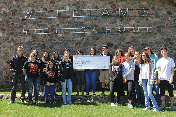 Alyson Fritsinger hands the $1,000 check to the Williams High School Student Council.