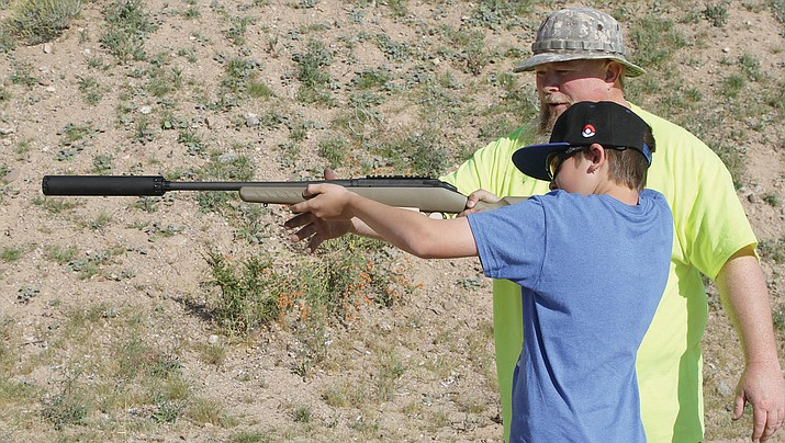 Colton Meredith, 10, prepares to fire a rifle with a silencer on it, as Chris Wagner instructs him during Kingman Range Days April 8.