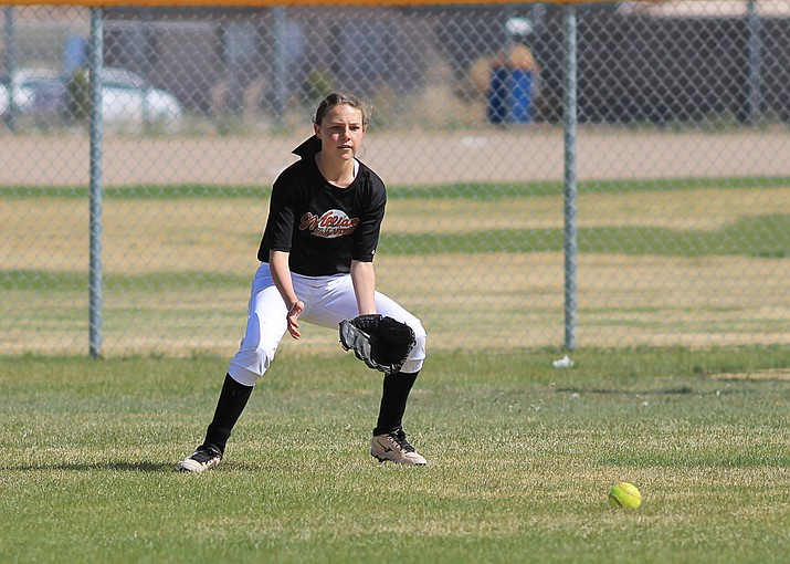 Maegen Ford fields a ball in the outfield.