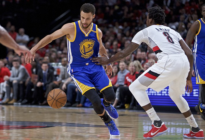 Golden State Warriors guard Stephen Curry, left, dribbles around his back past Portland Trail Blazers forward Al-Farouq Aminu during the first half of Game 4 Monday, April 24, in Portland, Ore. (Craig Mitchelldyer/AP)
