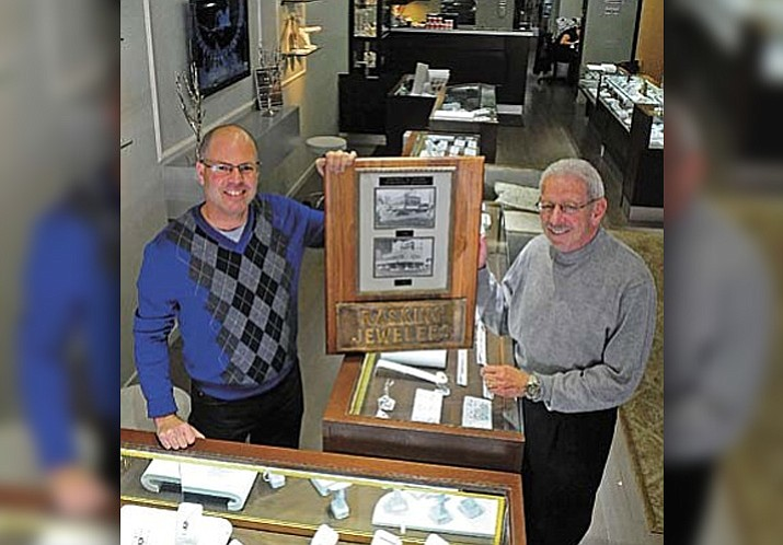 Greg Raskin, owner of Raskin's Jewelers in downtown Prescott and his father Lynn hold up a pair of photos of their Phoenix locations in 1946 and 1951 before their move to Prescott Thursday morning. Lynn first opened Raskin's Jewelers in Prescott on Goodwin Street in 1963. (Matt Hinshaw/The Daily Courier)
