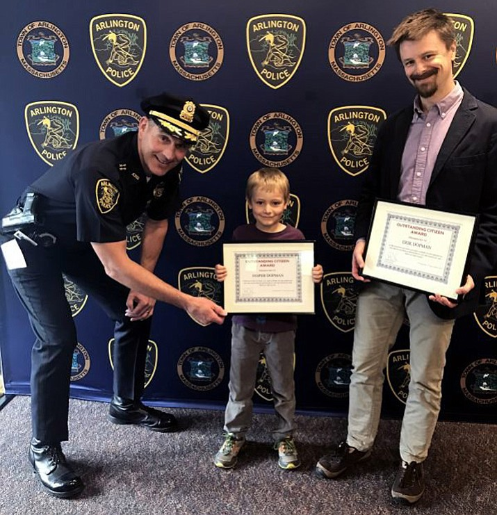 "In this photo provided by the Arlington Police Department, Chief Ryan presents Jasper Dopman and his father, Erik, with ""Outstanding Citizenship Awards"" on Thursday, April 27, 2017, in Arlington, Mass. The pair received the awards for turning in $2,000 in cash they found in a bank bag lost by a restaurant."