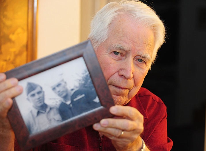 Prescott Valley resident Peter Marshall holds up a photo of his brother and himself taken on the day he came home from being a POW. Marshall a World War II veter an was a POW for 1368 days during the war. (Les Stukenberg/The Daily Courier)