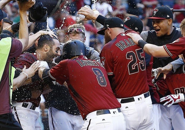 Arizona Diamondbacks' Daniel Descalso, left, celebrates his walkoff two-run home run against the Colorado Rockies with Chris Iannetta (8), Archie Bradley (25) and other teammates at home plate during the 13th inning of a baseball game Sunday, April 30, in Phoenix.