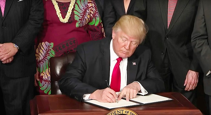 President Donald Trump signs an executive order. Photo courtesy of the White House