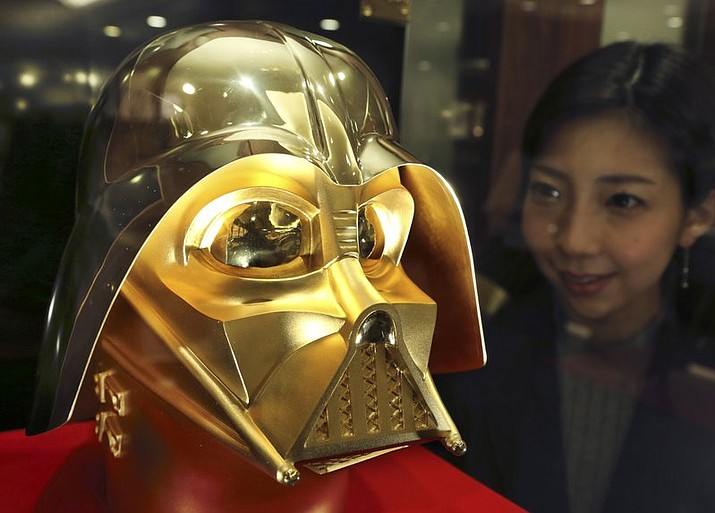 Tokyo gold jeweler Ginza Tanaka employee Momoko Marutani looks at the gold mask of Darth Vader at the jewelry shop in Tokyo, Monday, May 1, 2017. The life-size mask of Star Wars villain Darth Vader will be up for sale for a hefty price of 154 million yen ($1.38 million). The 24-karat mask was created by the gold jeweler to mark the 40th anniversary since the release of the first Star Wars film.