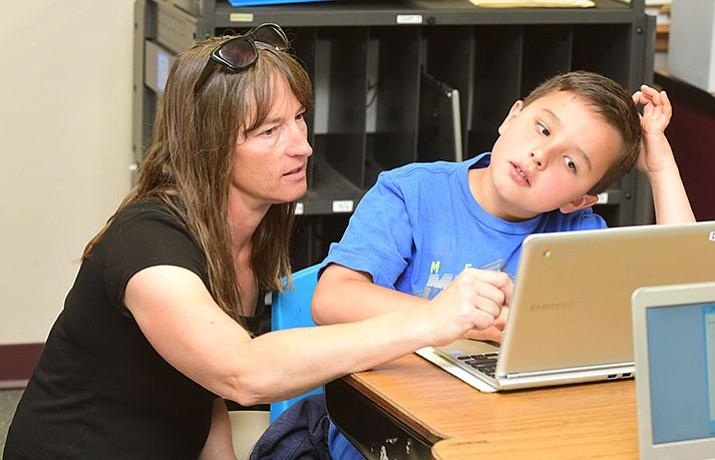 Third grade teacher Shelly Helmken helps Seth Vermilyea at Taylor Hicks Elementary School in Prescott Tuesday, May 2.  (Les Stukenberg/Courier)