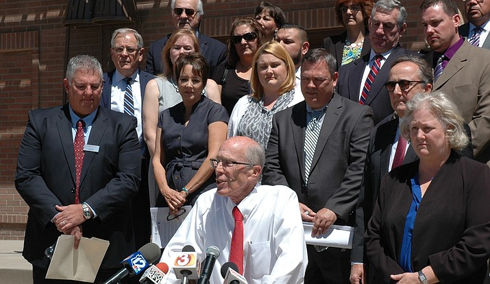 Surrounded by school officials and taxpayers, attorney Tim Hogan details Monday the elements of a lawsuit charging the state is not living up to its constitutional obligations to properly fund school construction and repairs. (Capitol Media Services photo by Howard Fischer)