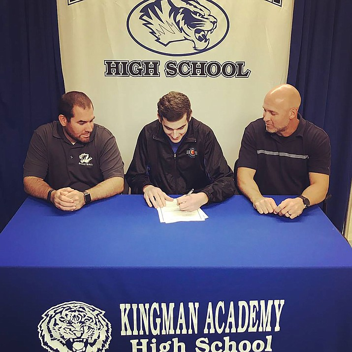 Kingman Academy's Cade Martin signed to play basketball at Chandler-Gilbert Community College Tuesday. Pictured from left are KAHS athletic director Michael Perrine, Martin and his father and principal, Jeff Martin.
