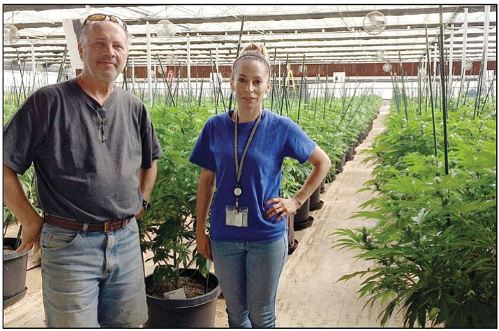 Michael O'Connor-Masse, owner, and Elizabeth Cruz, inventory manager, standing in one of their two greenhouses. (Sue Tone/Courier)