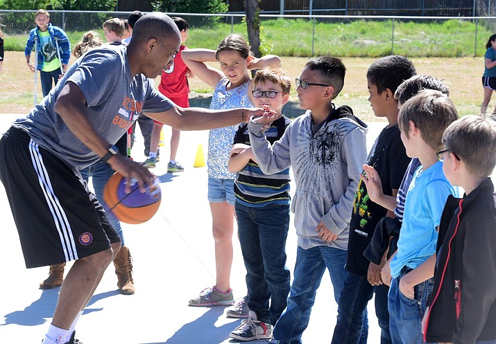 Northern Arizona Suns Head Coach Ty Ellis works with fourth grade students in a basketball camp at Taylor Hicks Elementary School on Tuesday, May 2, in Prescott. (Les Stukenberg/Courier)